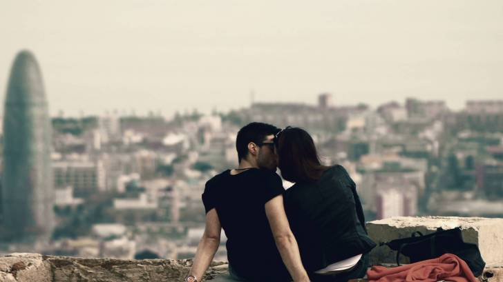 couple sharing a kiss overlooking barcelona