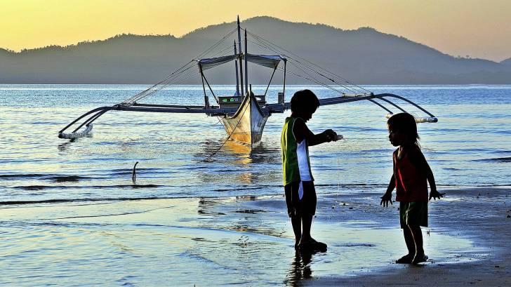 filipino children playing on the beach fishing