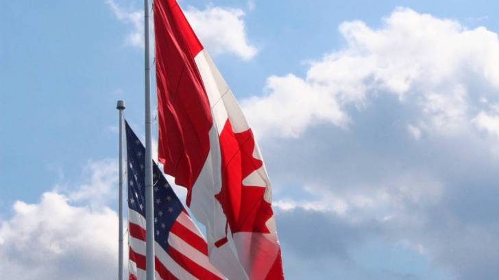 us and canada flags flying together