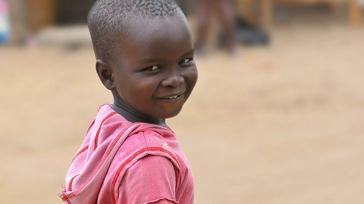 young african boy smiling in a red shirt