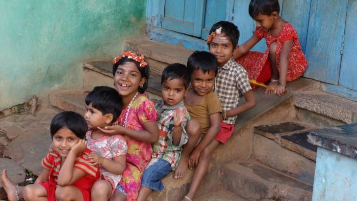 Indian children sitting on steps, happy