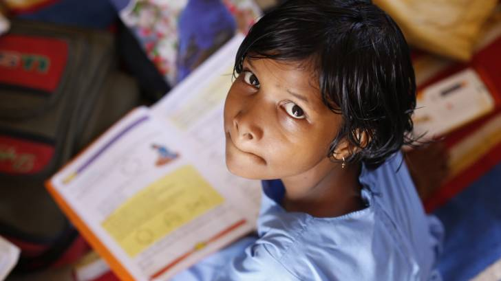 young idian girl studying, looking up at the camera
