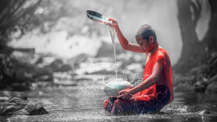 monk getting clean water out of a stream
