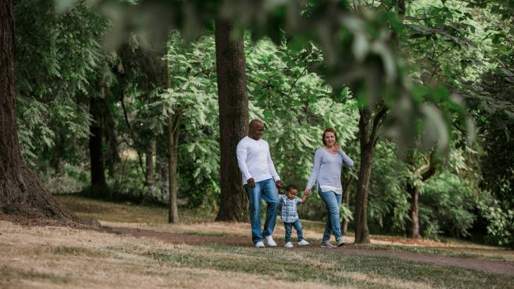 mom dad and baby walking through woods