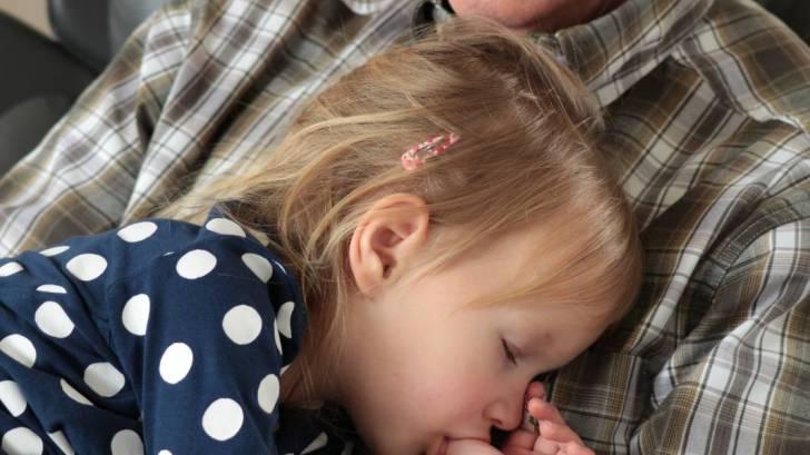 grandpa holding a sleeping grandchild