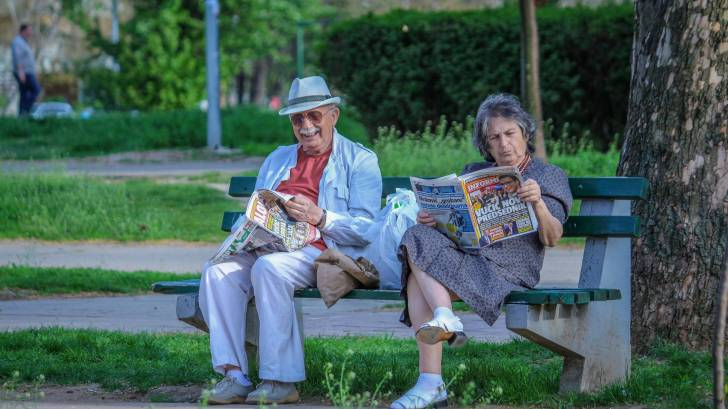 senior couple sitting on park bench reading paper