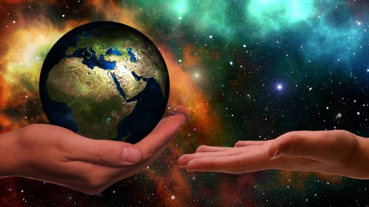 hands passing the earth to each other