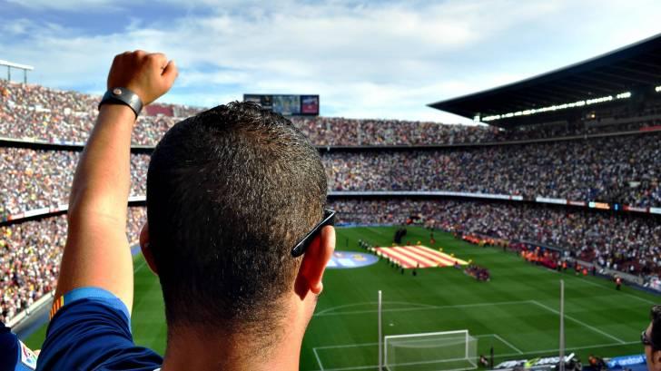 man cheering at the barcelona football stadium