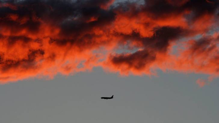 plane flying in the red sky
