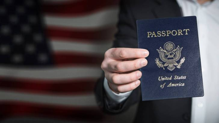 man holding a passport with the american flag in the back ground