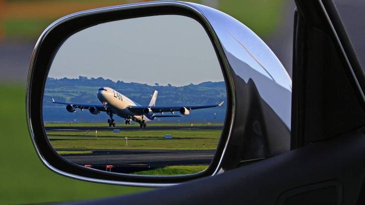 plane in a rear view mirror of a car taking off