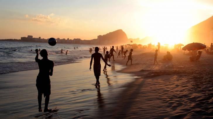 beach in rio, people playing, sun setting
