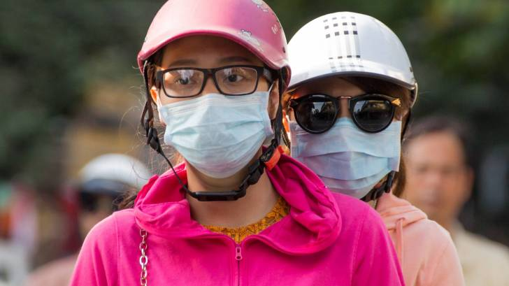 people with flu protective masks on a scooter