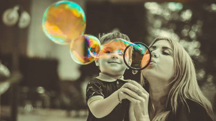 mom blowing bubbles with son who is happy and healthy