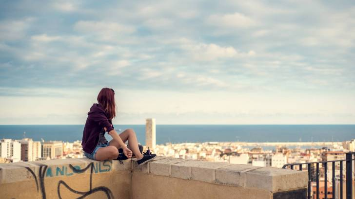 girl on a wall looking over a spanish city and to the ocean
