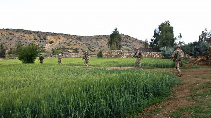 Troops walking through a field