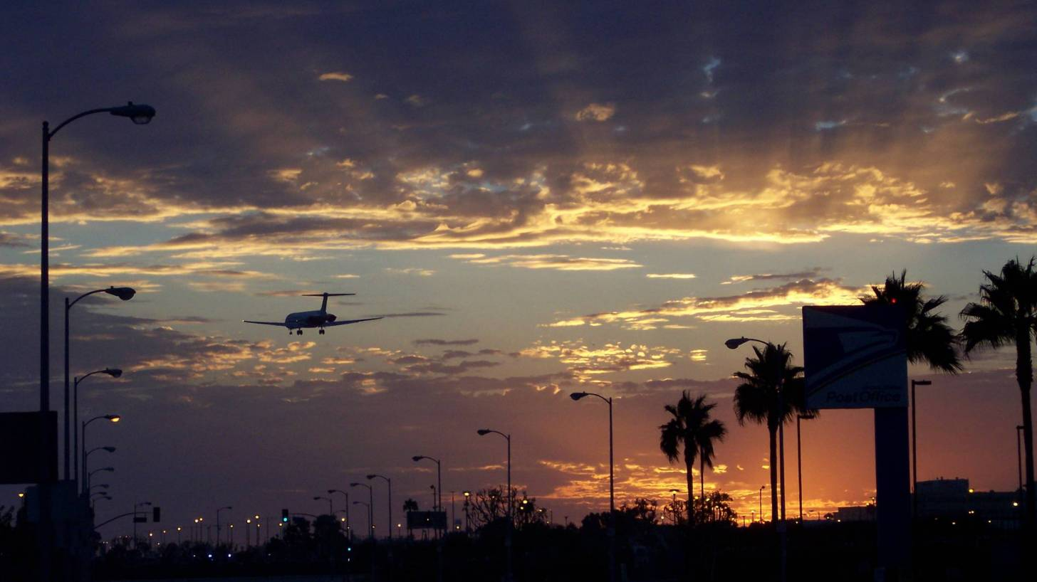 international jet landing at lax at sundown