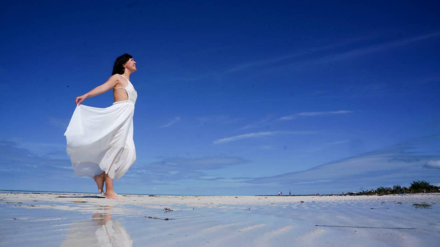 woman on beach celebrating the sun