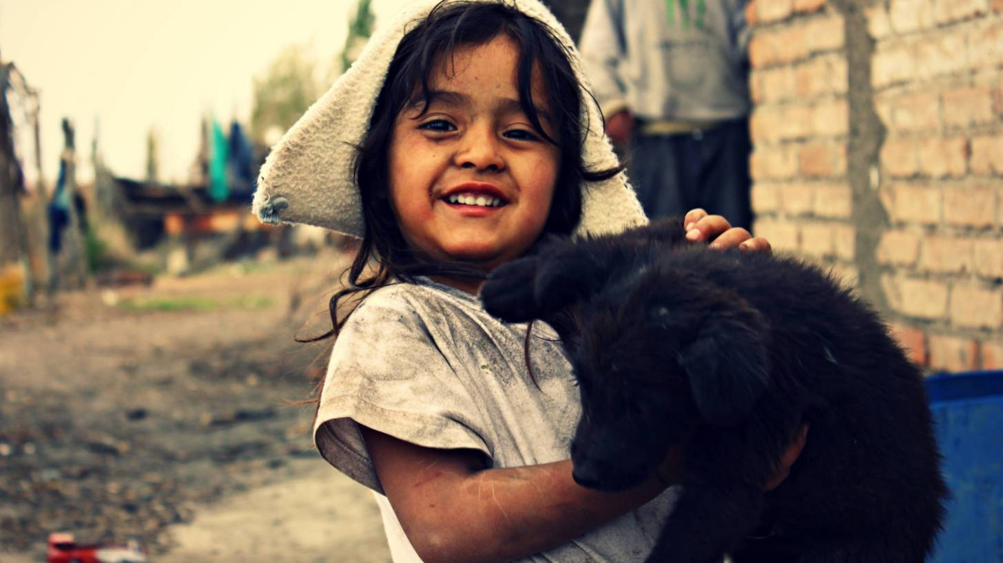 young girl in poverty holding black puppy, smiling