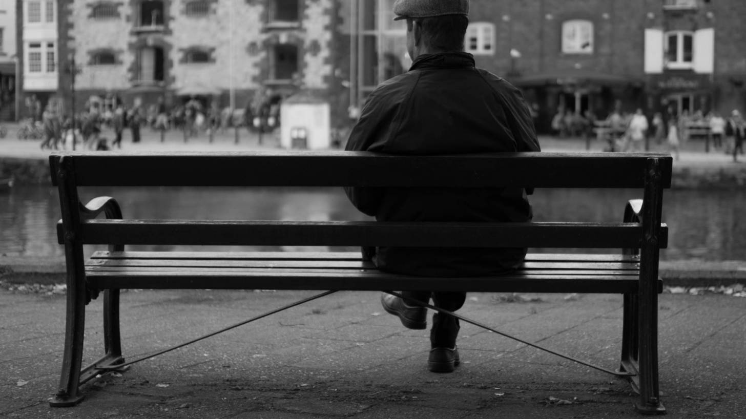 old english man sitting on a bench in the UK