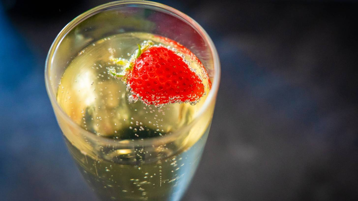 champagne glass with a strawberry fizzing