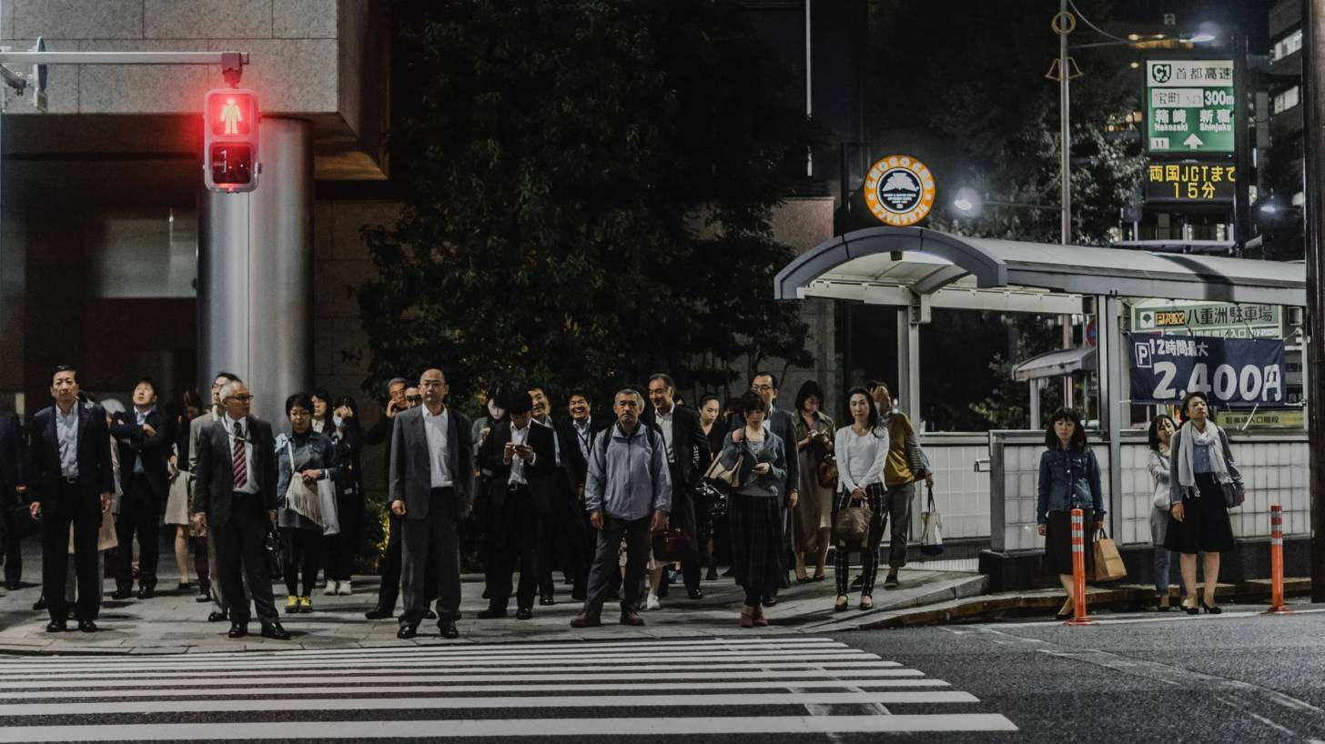 japanese crowd waiting to cross the road, mainly men
