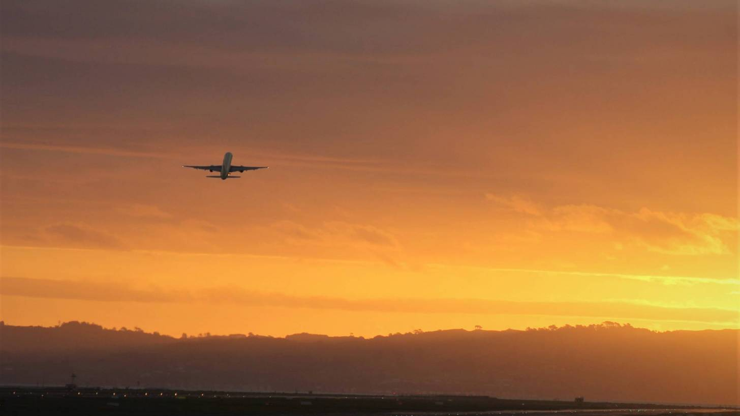 plane taking off in the sun set