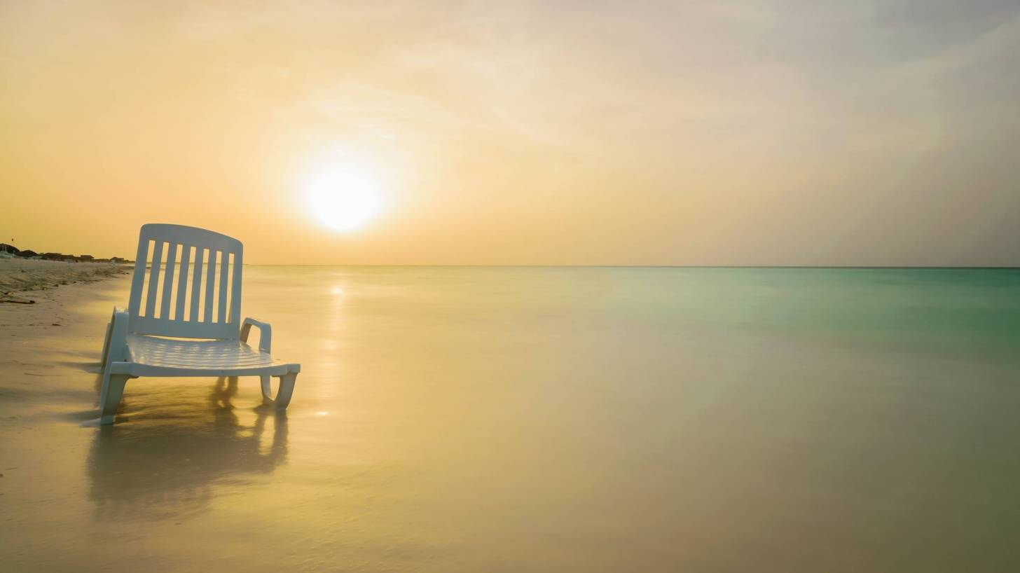 lone chair with sun setting over calm beach