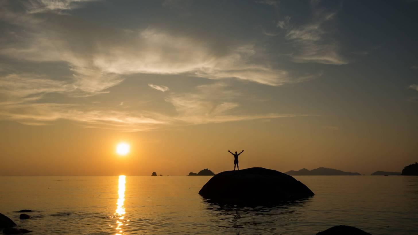 sun setting in the southern hemisphere, man celebrating on a rock