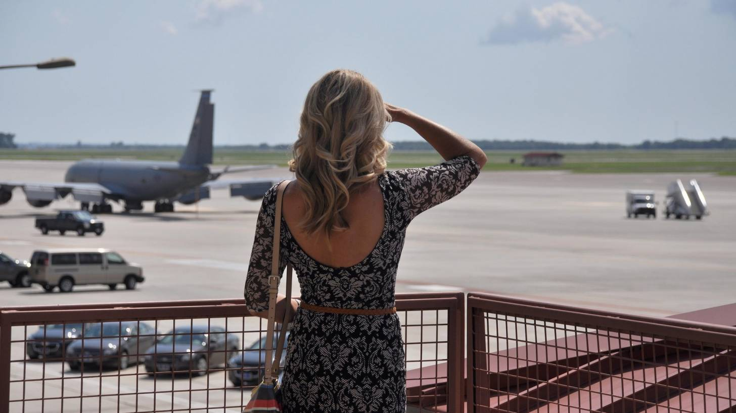 woman looking at an airport waiting for plane