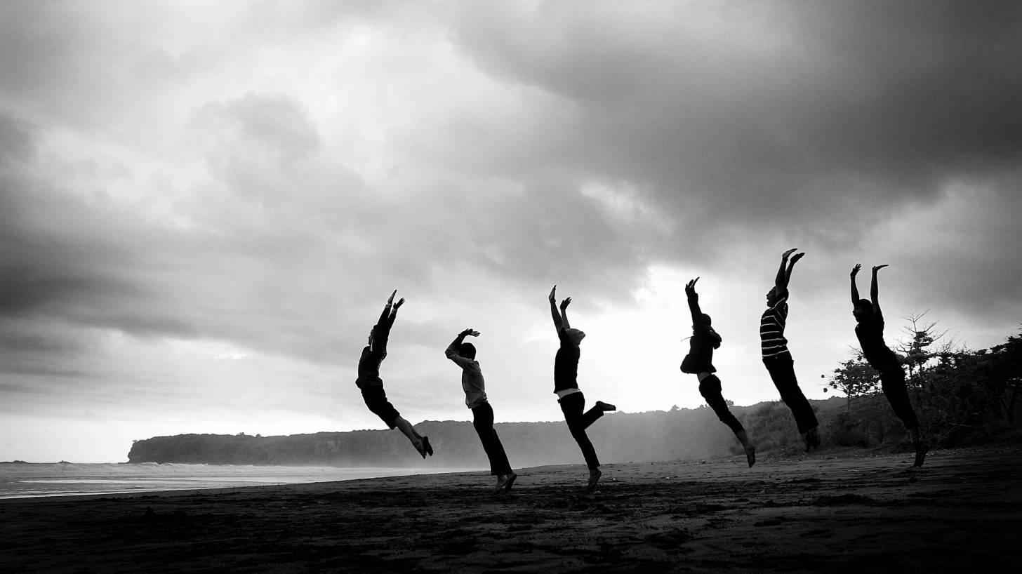 women jumping nn beach