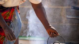 zimbabwe woman cooking over outdoor fire