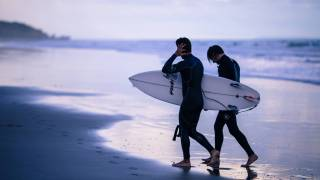 men going surfing at dusk