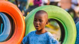 young boy happy standing by colored tires