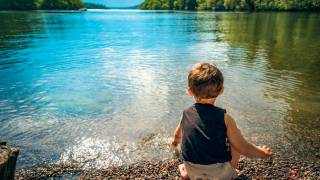 young boy sitting on the edge of a calm lake