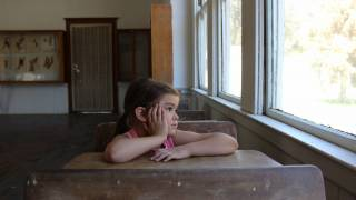 young girl in school looking out the window
