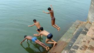 boys diving into river in India, hot weather