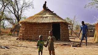 african village huts and family
