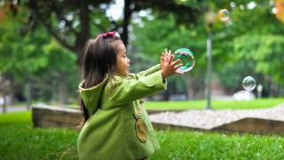 young girl chasing a soap bubble
