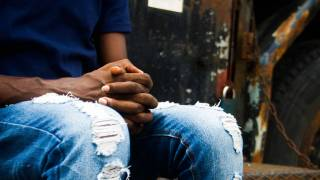 black man holding hands hopeful