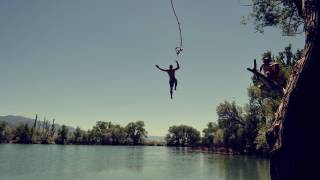 man swinging from a rope over a lake and letting go