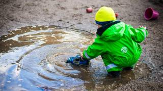 healthy child playing with a truck in a puddle