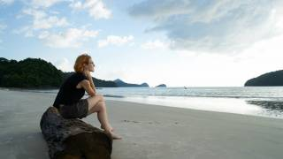 woman sitting on rock near sea