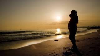 pregnant mom om beach at sunset