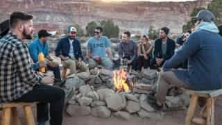men and women sitting around an outdoor camp fire