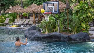 boy playing basketball in the pool