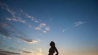 pregnant woman looking at beautiful florida sky