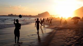beach in rio, people playing, sun setting