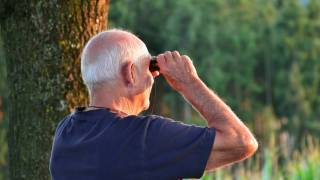 senior man with binoculars walking in the woods
