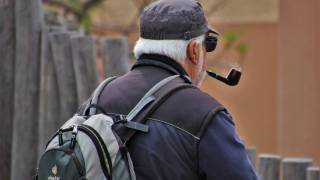older man puffing on pipe taking a walk